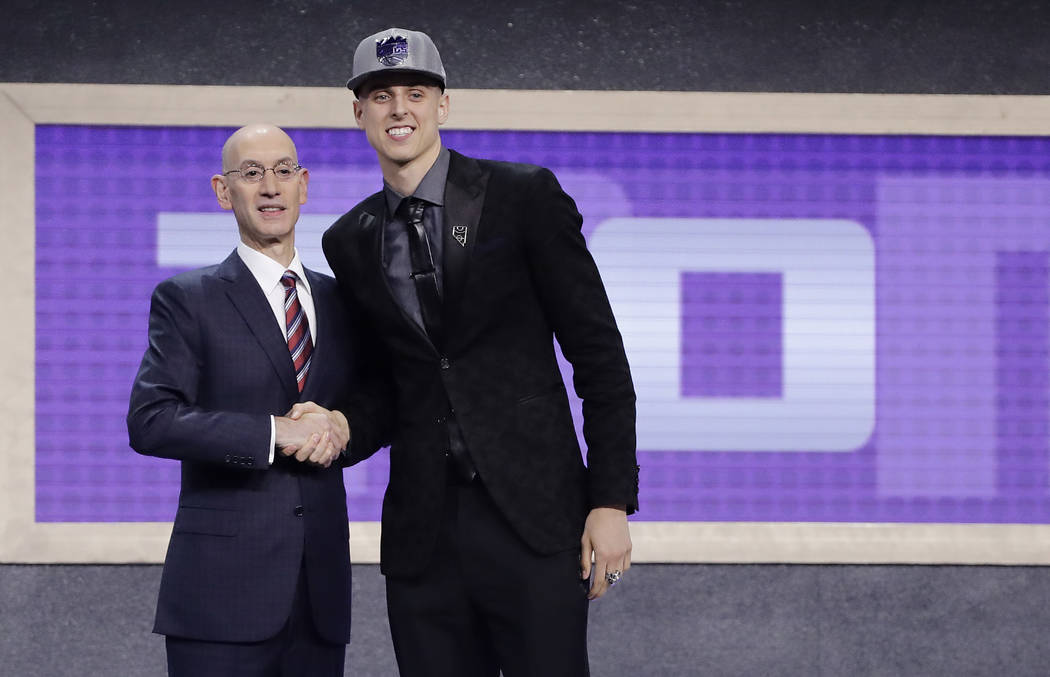 Zach Collins poses for photos with NBA Commissioner Adam silver after being selected by the ...