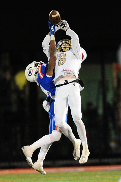 Bishop Gorman coronrback Alex Perry, left, breaks up a pass intended for Faith Lutheran wide ...