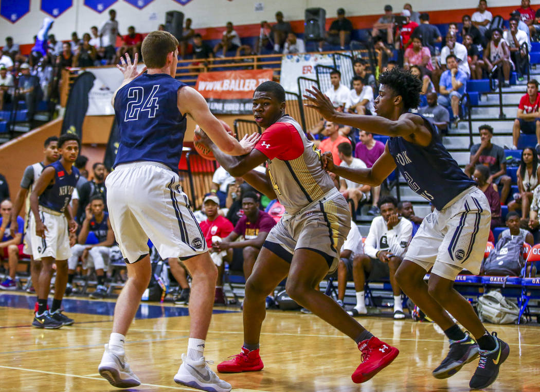 Team Thad's Javian Fleming, center, defends the ball against New York defenders Sloan ...