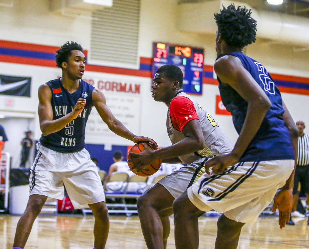Team Thad's Javian Fleming , center, defends the ball against New York defenders Bryce ...