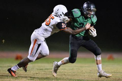 Virgin Valley running back Jayden Perkins (33) tries to shed a tackler during the Virgin Val ...