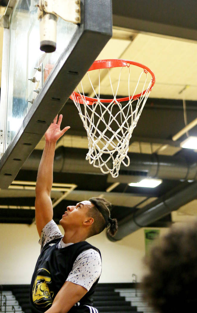 Clark High School senior Greg Foster completes a lay up during basketball practice at Clark ...