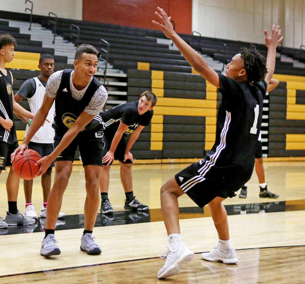 Clark High School senior Greg Foster prepares to pass the ball while Frank Collins guards du ...