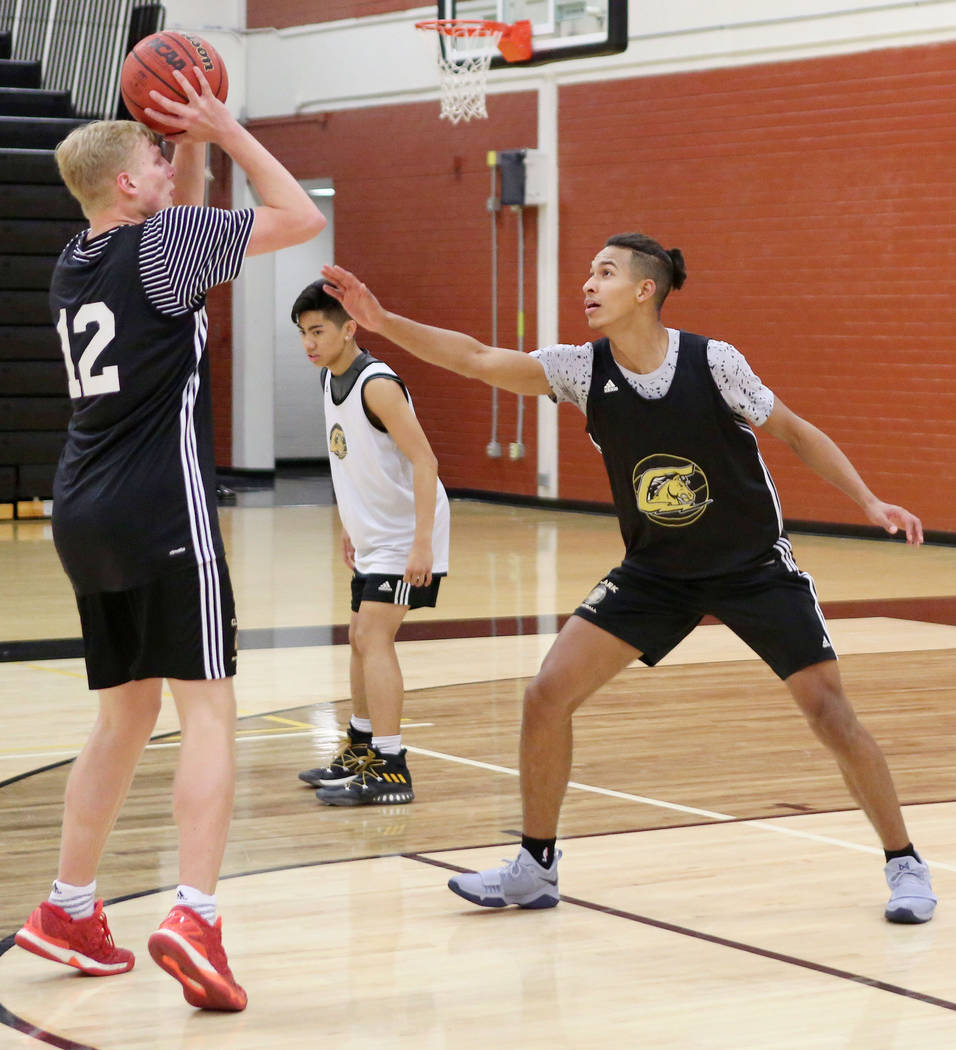 Trey Woodbury, 12, shoots while Greg Foster guards during basketball practice at Clark High ...