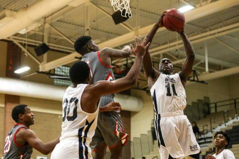 Democracy Prep's Jared Holmes (11), right, receives a rebound against Arbor View durin ...