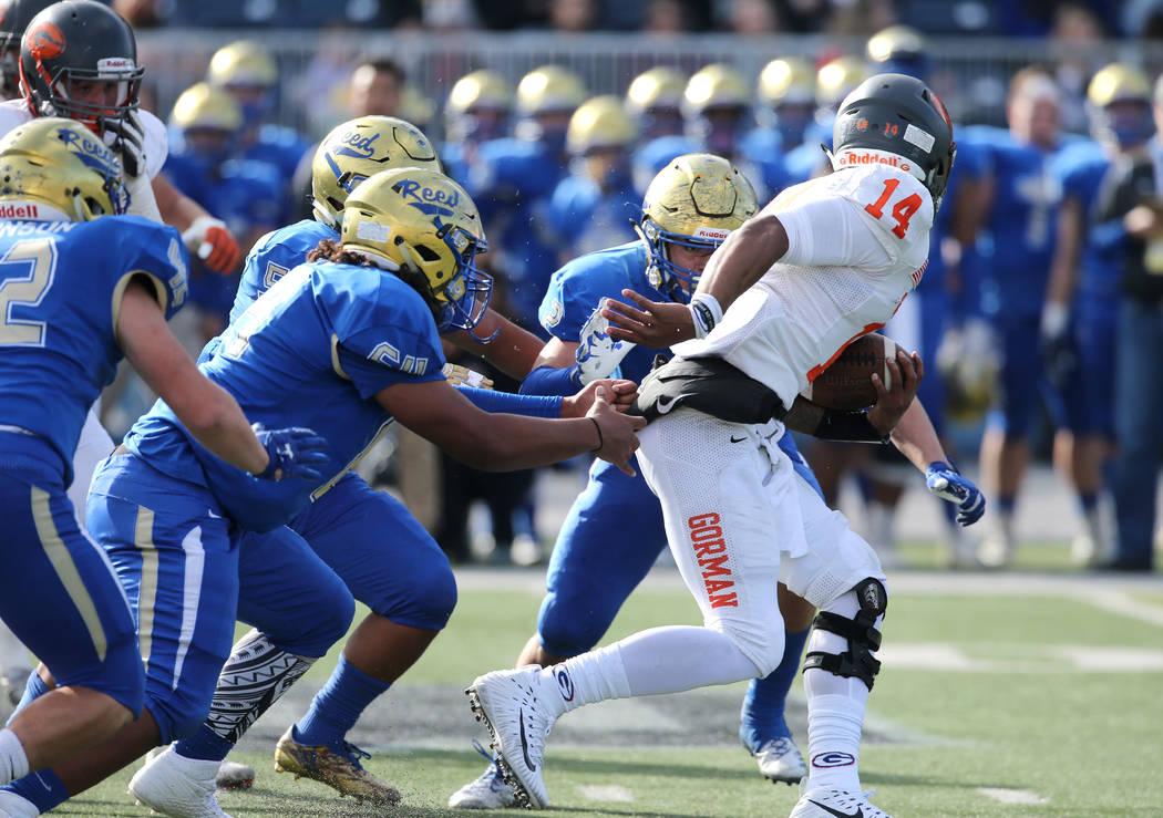 Bishop Gorman's quarterback Dorian Thompson-Robinson scrambles under pressure from Ree ...