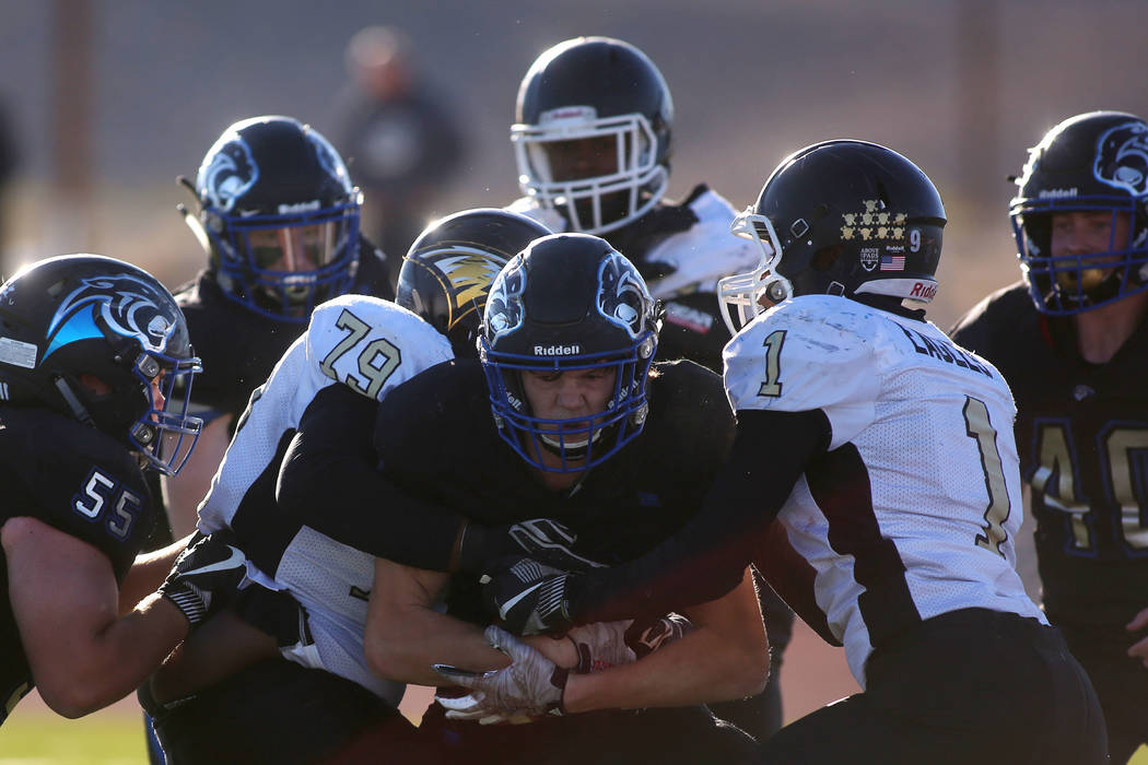 Spring Mountain players attempt to take down Pahranagat Valley player Richard Lewis (19) dur ...