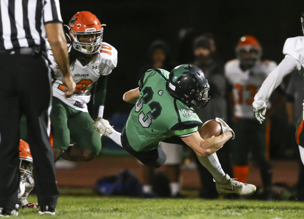Virgin Valley's Jayden Perkins (33) gets tripped up by Mojave during the Class 3A stat ...