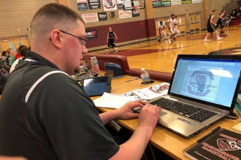 Desert Oasis assistant coach Dave Aikman working on his computer during the Tri-State Invita ...