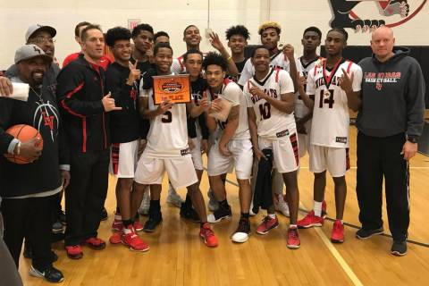 Las Vegas players and coaches pose with the Las Vegas Prep Championship trophy after beating ...