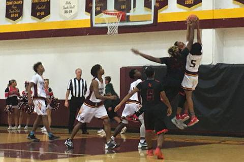 Eldorado and Las Vegas High players fight for the ball during their boys basketball game at ...