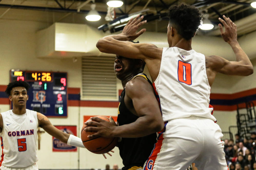 Clark Chargers' Antwon Jackson (23) is guarded by Bishop Gorman's Isaiah Cottrel ...