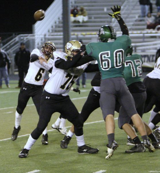 Faith Lutheran quarterback Jacob Deaville (6) unloads a pass as teammate Austin Prather (75) ...
