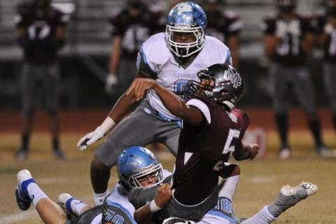 Cimarron's Derek Morefield (5) loses the ball after being tackled by Centennial defend ...
