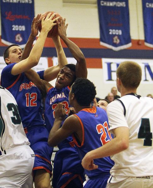 Gorman's Zach Collins (12) and Nick Blair (23) both grab a rebound as teammate Deon Wh ...