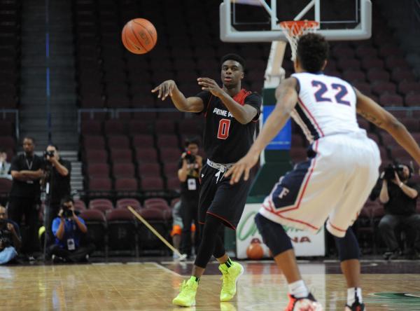 Prime Prep Academy basketball player Emmanuel Mudiay, left, passes the ball as Findlay Prep& ...
