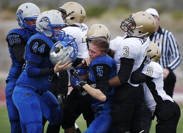 Pahranagat Valley's Wade Leavitt (5) is wrapped up as his helmet flies off and is caug ...