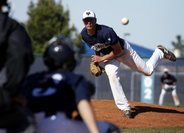 Spring Valley's Dylan Drachler throws as his brother Zane awaits the pitch.