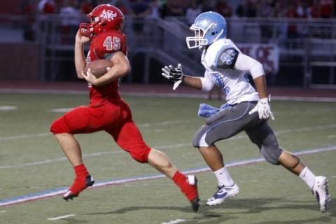 Arbor View running back Ricky Clark runs ahead of Centennial defensive back Samuel Liaga for ...
