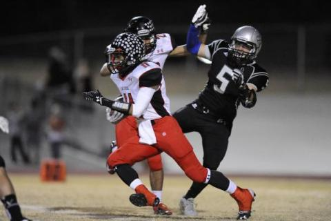 Las Vegas High wide receiver Aaron Zanin-Banks, front, returns a kick during the first quart ...