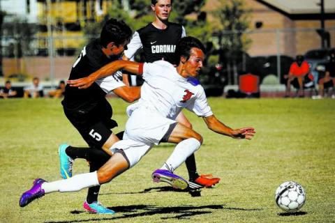 Liberty forward Danny Musovski battles past a pair of Coronado defenders to score a goal on ...