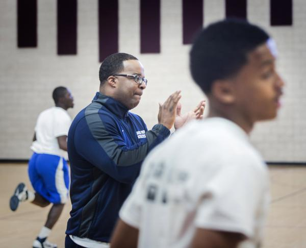 Agassi Prep basketball coach Trevor Diggs encourages playes during practice on Monday.