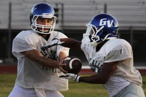 Green Valley quarterback Christian Lopez hands the ball off during practice. Lopez and the G ...
