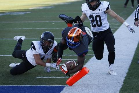 Daniel Stewart of Bishop Gorman dives into the end zone between Palo Verde's Darrion F ...