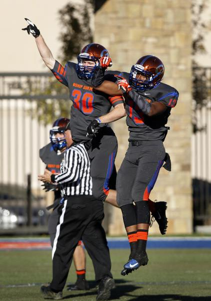 Dylan Weldon (30) of Bishop Gorman celebrates with teammate Armand Perry (13) after one of W ...