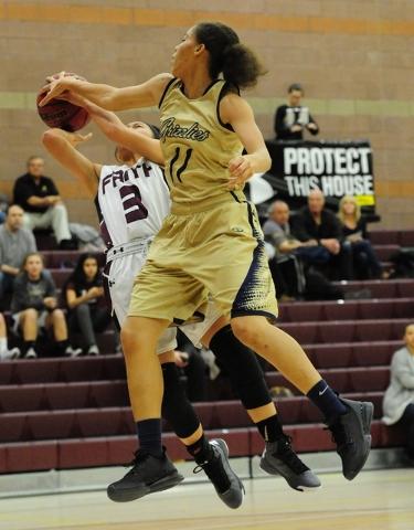 Spring Valley guard Kayla Harris (11) blocks the shot of Faith Lutheran guard Maddie Bocobo ...