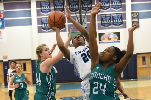 Canyon Springs Alexa Thrower (20) goes up for a shot against Rancho defenders Samantha Pocho ...
