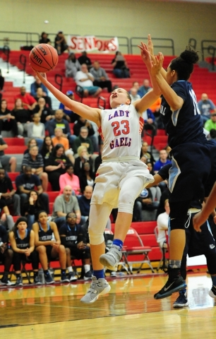 Bishop Gorman guard Megan Jacobs (23) goes up for a shot against Centennial guard Jayden Egg ...