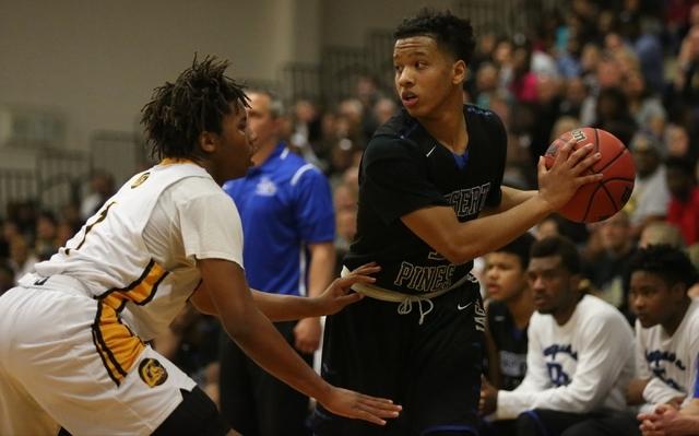 Desert Pines High School junior Capri Uzan (1) looks for an open teammate while being guarde ...