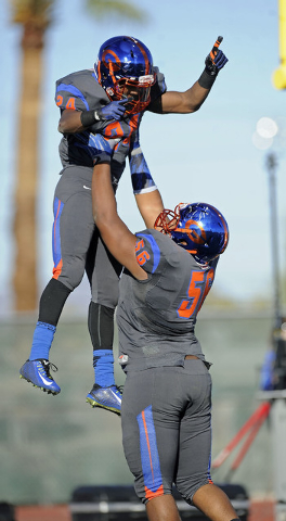 Bishop Gorman offensive guard Jackson Perry (56) hoists running back Russell Booze (24) afte ...