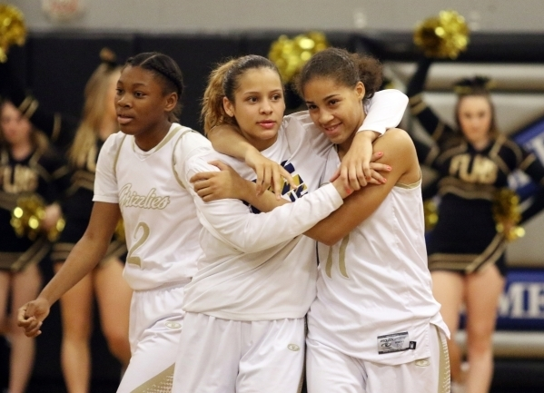 Essence Booker (center) and Kayla Harris share a hug during a game last season. (Ronda Churc ...