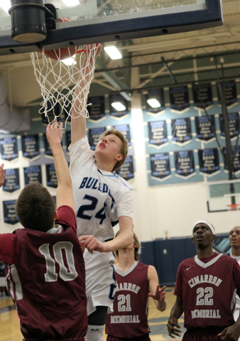 Centennial forward Garett Scheer (24) goes up for a shot over Cimarron-Memorial guard Austin ...
