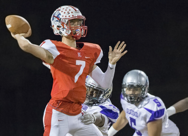 Liberty's Kenyon Oblad (7) makes a pass with Silverado defenders on his back during th ...