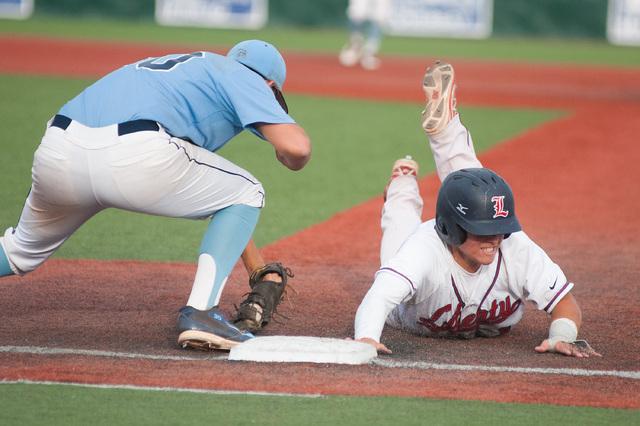Liberty's Josh McCollum dives back to first base while Centennial's Travis Steve ...
