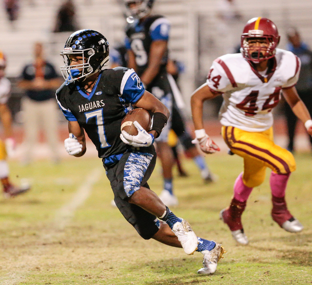 Desert Pines senior Isaiah Morris (7) runs the ball down the field as Del Sol sophomore Ati ...