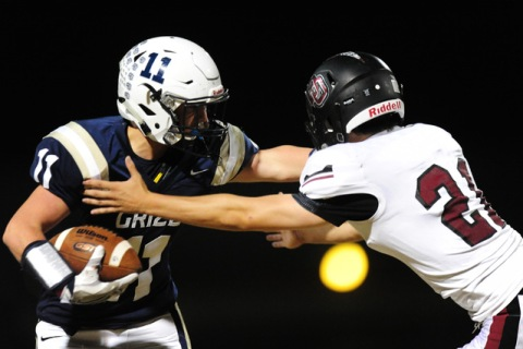 Spring Valley wide receiver Kash Jenkins (11) is tackled by Desert Oasis safety Blake Ricka ...