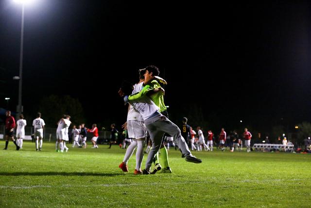 Coronado Cougars soccer team goalkeeper, Harrison Skinner, is hugged by teammates at the Bet ...