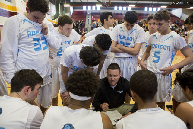 Adelson basketball team huddles for a timeout during the 2A boys state semifinal game at Del ...