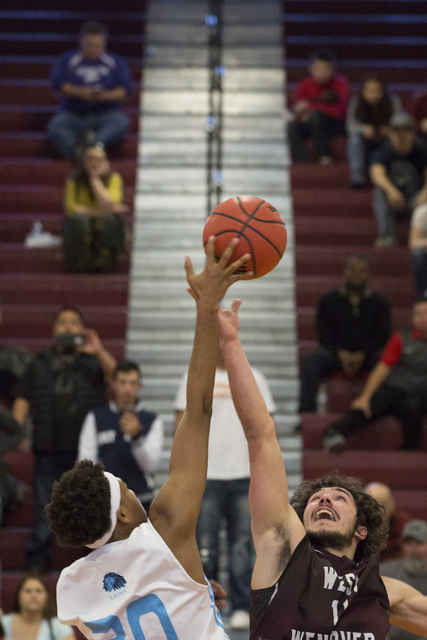 Adelson junior Miles Hagan, left, and West Wendover senior Zade Elton, right, fight for the ...