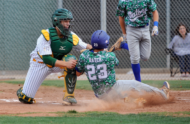 Green Valley's Anthony Hatch (23) is tagged out at home plate by Rancho catcher Zach B ...