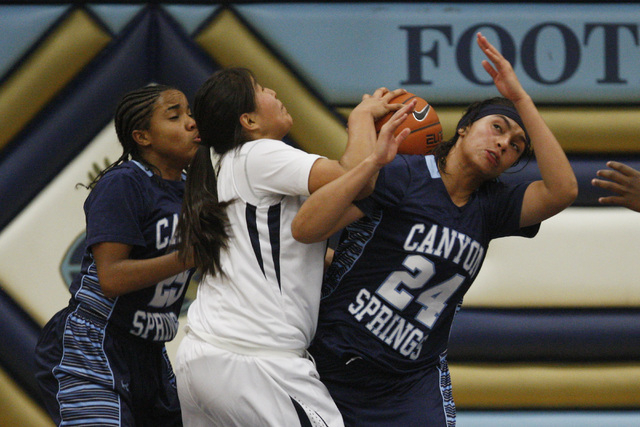 Canyon Springs' D'Licya Feaster, left, and Daijhan Cooks fight for a rebound wit ...