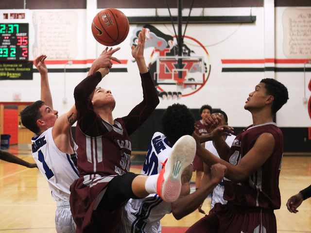 Basic guard Jared Meacham and Cimarron-Memorial center Joe Tito compete for a rebound during ...