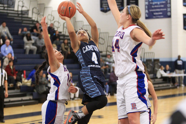 Canyon Springs guard Alize Bell drives between Reno guard Daranda Hinkey, left, and center M ...