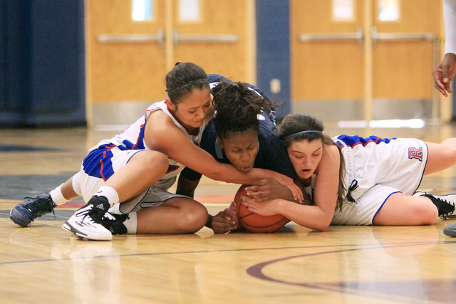 Canyon Springs guard Alexia Thrower fights for a loose ball with Reno guard Daranda Hinkey, ...