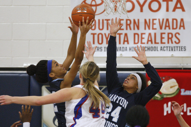 Canyon Springs guards Mia Moss, left, and Daijhan Cooks grab a rebound from Reno center Mall ...