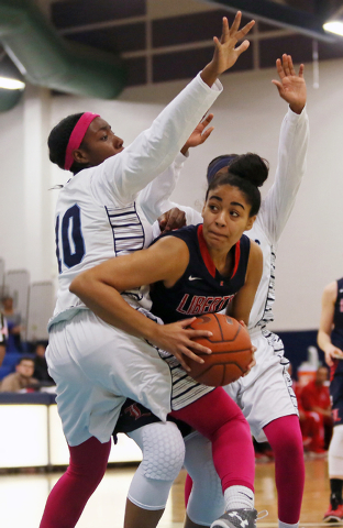 Liberty's Paris Strawther, center, gets tangled up with Canyon Springs defense Dre&#82 ...